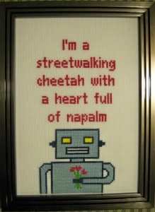"Crossstich image with a robot holding flowers and the text ""I'm a streetwalking cheetah with a heart full of napalm."" No Really."