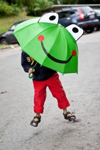 child with a frog umbrella